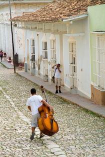 Man walking down Simon Bolivar and carrying a cello von Sami Sarkis Photography