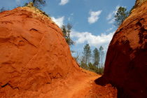 Narrow passage between two bright red sandy cliffs by Sami Sarkis Photography