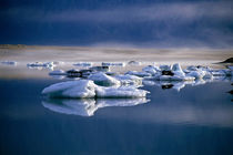Floating icebergs reflected in the quiet waters of Jokulsarlon by Sami Sarkis Photography