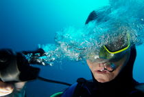 One scuba diver pulls the breathing regulator out of his mouth while still underwater von Sami Sarkis Photography