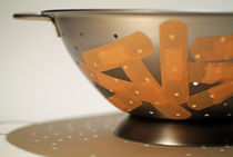 Metallic colander covered with sticking plasters. von Sami Sarkis Photography