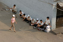 Restaurant workers having a break outside as a woman walks past von Sami Sarkis Photography