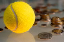 Tennis ball next to numerous piles of coins. by Sami Sarkis Photography