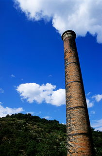 Brick smoke stack emitting smoke by Sami Sarkis Photography