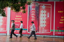 Men walking past a huge advertisement while walking down the street together in Beijing von Sami Sarkis Photography
