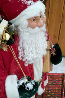 Santa Claus toy standing next to Christmas presents in the snow. by Sami Sarkis Photography