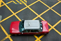 Red taxi cab driving over yellow lines by Sami Sarkis Photography
