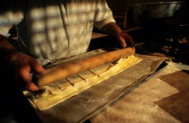 Baker rolling pastry with a rolling pin inside a bakery von Sami Sarkis Photography