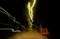 Blurred tail lights of highway traffic at night. by Sami Sarkis Photography