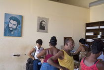 Customers at a pharmacy with Che Guevara portraits on the walls von Sami Sarkis Photography