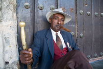 Portrait of a man wearing a 1930s-style suit and smoking a cigar by Sami Sarkis Photography