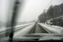 Car driving on a snowy road in the winter. by Sami Sarkis Photography