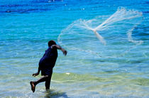 Man launching his fishing net into the crystal water von Sami Sarkis Photography