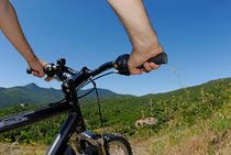Hands on mountain bike by a landscape by Sami Sarkis Photography