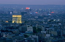 Arc de Triomphe illuminated at twilight surrounded by the cityscape of Paris by Sami Sarkis Photography