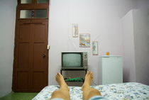 Man's legs on a bed in front of an old TV at a guesthouse by Sami Sarkis Photography