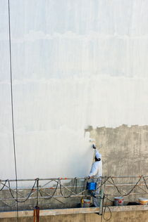 Man painting the facade of a building by Sami Sarkis Photography