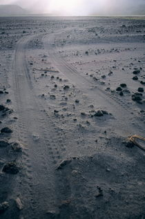 Tyre tracks and lava rocks on the vast ash plain near Mount Yasur by Sami Sarkis Photography