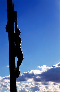 Statue of Jesus Christ on the cross against a cloudy sky. von Sami Sarkis Photography