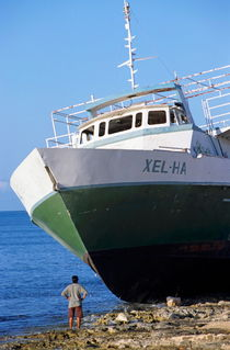 Man looking up at a beached passenger ship on Cozumel Island von Sami Sarkis Photography
