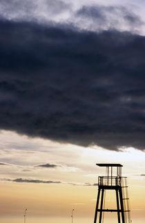 Storm clouds gathering over a lifeguard tower at sunset von Sami Sarkis Photography