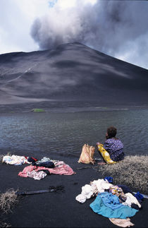 Girl washing clothes in a lake with the Mount Yasur volcano emitting smoke in the background von Sami Sarkis Photography