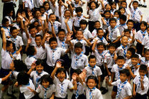 Bangkok school children jumping and smiling at the camera by Sami Sarkis Photography