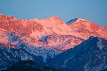 Snowy mountain range with a rosy hue at sunset. von Sami Sarkis Photography