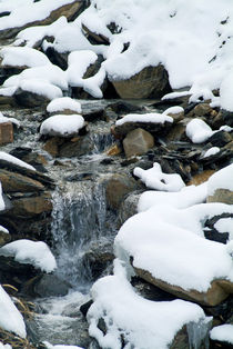 Snow-covered rocks beside a mountain stream in the French Alps von Sami Sarkis Photography