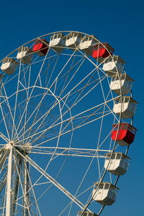 Red and white empty carriages on a ferris wheel at an amusement park. by Sami Sarkis Photography