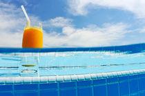 Glass of orange juice on pool ledge by Sami Sarkis Photography