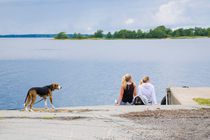 Two girls and a dog wating for the passenger boat  von kbhsphoto