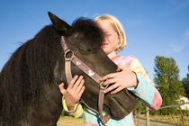 Young blond girl hugging her black pony by kbhsphoto