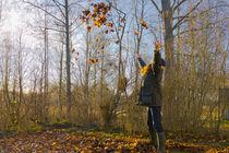 Woman throwing autumn leaves in the air von kbhsphoto
