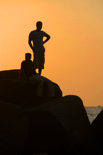 Silhouetted Figures on Rock at Sunset Palolem by serenityphotography
