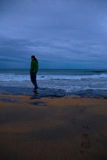 Young man standing on the beach of Fanore, County Clare, Ireland at dusk von kbhsphoto