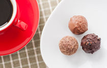 Three chocolate truffles and a red coffee cup by Lars Hallstrom