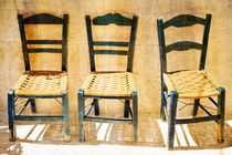 Three-blue-empty-wooden-chairs-on-sidewalk-in-matala-2