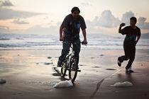 Teens riding a bike on the beach von Jacobo Zanella