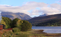 Steam train travelling towards Ben Nevis, Loch Eil, Scotland by Linda More
